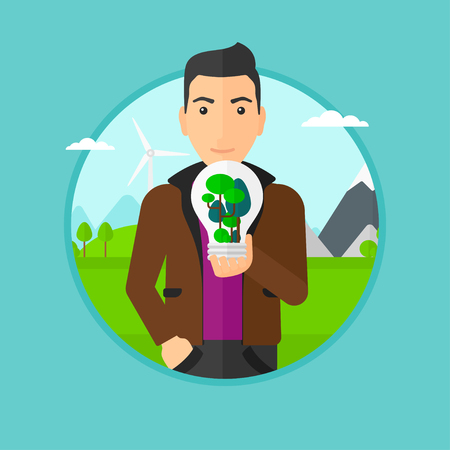 Man holding light bulb with tree inside. Man with light bulb and tree inside standing on a background with wind turbines. Vector flat design illustration in the circle isolated on background. Vettoriali