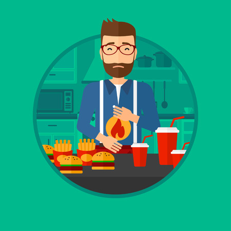 burn out: A hipster man suffering from heartburn. Man standing in the kitchen in front of table with junk food and suffering from heartburn. Vector flat design illustration in the circle isolated on background.