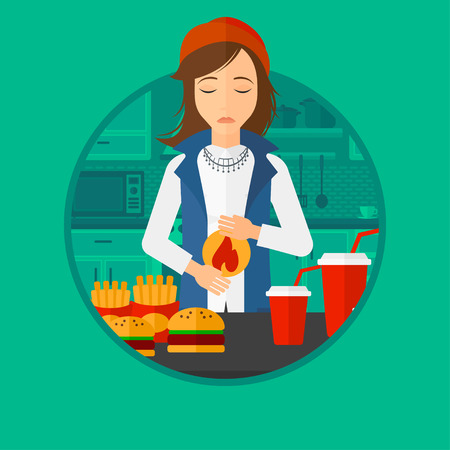 Young woman suffering from heartburn. Woman standing in the kitchen in front of table with junk food and suffering from heartburn. Vector flat design illustration in the circle isolated on background.