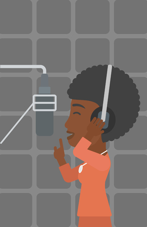 An african-american woman in headphones making a record of her voice in studio vector flat design illustration. Vertical layout. Vettoriali