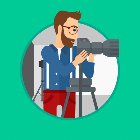 A hipster photographer with the beard working with camera on a tripod in photo studio. Photographer using camera in the studio. Vector flat design illustration in the circle isolated on background. 向量圖像