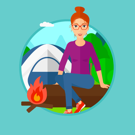 young woman sitting: Woman sitting on a log near a fire on a background of camping site with tent. Young woman sitting near a campfire at a campsite. Vector flat design illustration in the circle isolated on background.