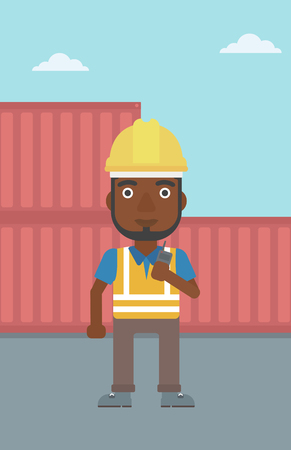 An african-american port worker talking on wireless radio. Port worker standing on cargo containers background. Man using wireless radio. Vector flat design illustration. Vertical layout. Stock Vector - 128543970