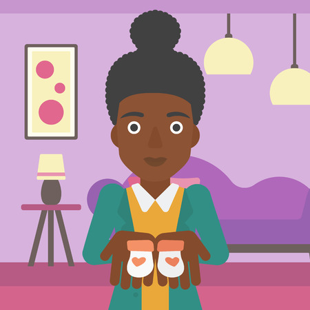 An african-american pregnant woman holding baby booties in hands on the background of living room. Vector flat design illustration. Square layout.