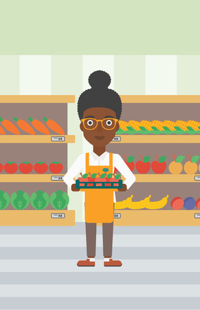 An african-american female supermarket worker holding a box with apples on the background of shelves with vegetables and fruits in supermarket. Vector flat design illustration. Vertical layout.