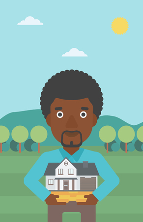 An african-american man holding house model in hands on the background of mountains. Real estate agent with house model. Vector flat design illustration. Vertical layout. 向量圖像