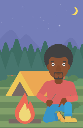 kindle: An african-american man kindling a campfire on the background of camping site with tent. Tourist relaxing near campfire. Vector flat design illustration. Vertical layout.