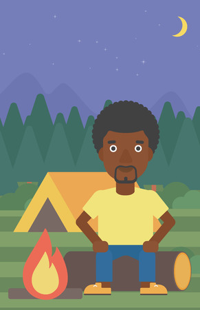 camping site: An african-american travelling man sitting on a log near a fire on a background of camping site with tent. Man sitting near a campfire at a campsite. Vector flat design illustration. Vertical layout.