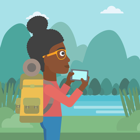 woman cellphone: An african-american woman taking photo of landscape with mountains. Young hiking woman with backpack taking photo with her cellphone. Vector flat design illustration. Square layout. Illustration
