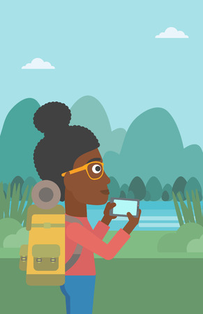 woman cellphone: An african-american woman taking photo of landscape with mountains. Young hiking woman with backpack taking photo with her cellphone. Vector flat design illustration. Vertical layout.