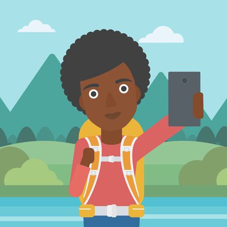 woman cellphone: An african-american woman making selfie on the background of mountains. Travelling woman with backpack taking photo with cellphone. Vector flat design illustration. Square layout. Illustration