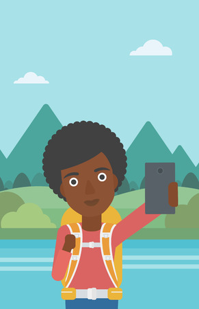 woman cellphone: An african-american woman making selfie on the background of mountains. Travelling woman with backpack taking photo with cellphone. Vector flat design illustration. Vertical layout.