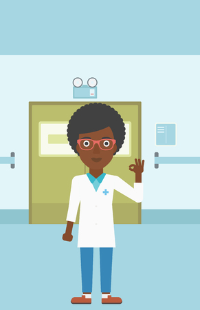 hospital corridor: An african-american young female doctor in medical gown showing ok sign in the hospital corridor. Vector flat design illustration. Vertical layout.