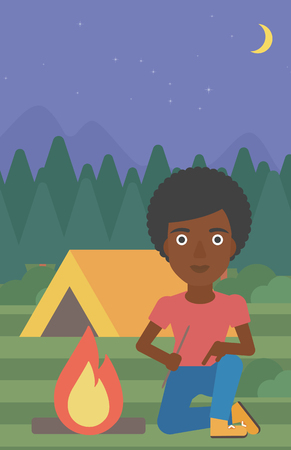 kindling: An african-american woman kindling campfire on the background of camping site with tent. Tourist relaxing near campfire. Woman sitting near campfire. Vector flat design illustration. Vertical layout. Illustration