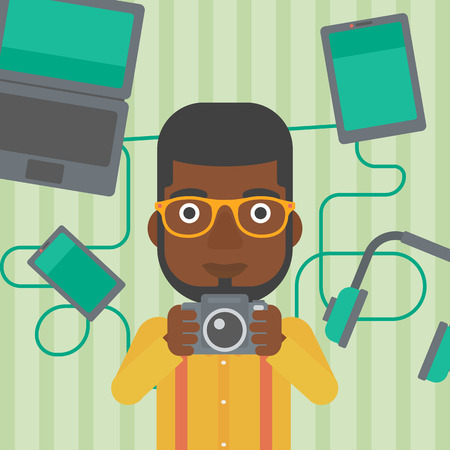 taking photo: An african-american man taking photo with digital camera. Man surrounded with gadgets. Man using many electronic gadgets. Vector flat design illustration. Square layout.