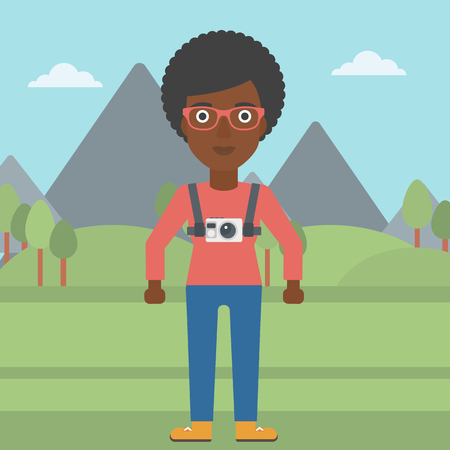 An african-american woman with a digital camera on her chest. Tourist with a digital camera standing on the background of mountains. Vector flat design illustration. Square layout. Reklamní fotografie - 59766946