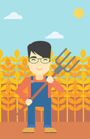 An asian smiling farmer holding a pitchfork. Farmer standing on the background of wheat field. Vector flat design illustration. Vertical layout.