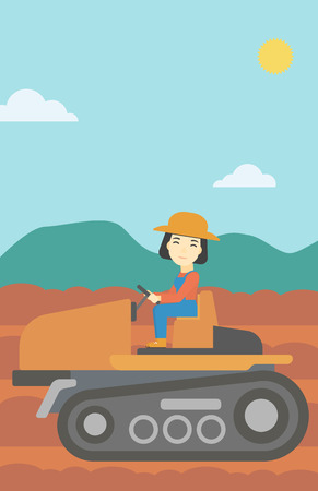 fieldwork: An asian female farmer driving a tractor on the background of plowed agricultural field. Farmer sitting on a tractor in the countryside. Vertical layout.