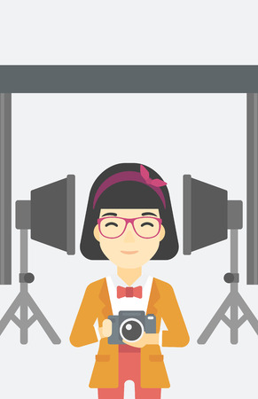 taking photo: An asian young photographer holding a camera in photo studio. Photographer using camera in the studio. Woman taking photo with digital camera. Vector flat design illustration. Vertical layout.