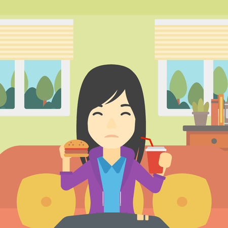 young woman sitting: An asian young woman sitting on a sofa while eating hamburger and drinking soda on the background of living room. Vector flat design illustration. Square layout.