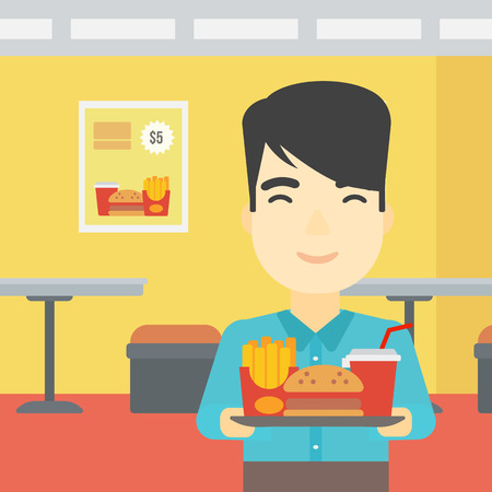 lunch tray: An asian young man holding tray full of junk food on a cafe background. Smiling man in fast food restaurant. Man having lunch in a fast food restaurant. Vector flat design illustration. Square layout. Illustration