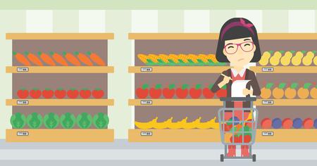 mujer en el supermercado: Una mujer reflexiva asiático de pie en el supermercado con el carro de supermercado lleno de productos y la celebración de una lista de compras en las manos. Vector de diseño plano ilustración. disposición horizontal. Vectores