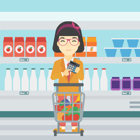 An asian young woman at the supermarket with calculator and supermarket trolley full with products. Woman checking prices with calculator. Vector flat design illustration. Square layout.