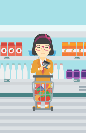 consumer goods: An asian young woman at the supermarket with calculator and supermarket trolley full with products. Woman checking prices with calculator. Vector flat design illustration. Vertical layout. Illustration