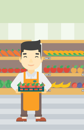 An asian young male supermarket worker holding a box with apples on the background of shelves with vegetables and fruits in supermarket. Vector flat design illustration. Vertical layout. Vettoriali
