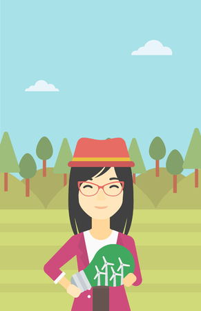 An asian woman standing on the background of green forest and holding in hands a big light bulb with small wind turbines inside. Green energy concept. Vector flat design illustration. Vertical layout. Vettoriali