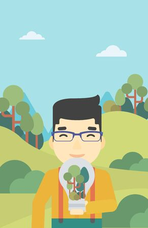 An asian man standing on the background of green forest and holding in hands a big lightbulb with trees inside. Green energy concept. Vector flat design illustration. Vertical layout.