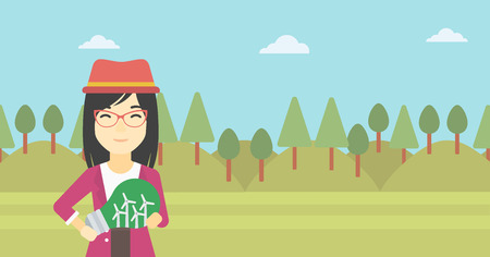 An asian woman standing on the background of green forest and holding in hands a big light bulb with small wind turbines inside. Vector flat design illustration. Horizontal layout.