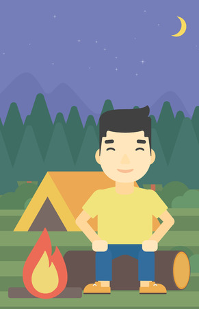 camping site: An asian travelling man sitting on a log near a fire on a background of camping site with tent. Man sitting near a campfire at a campsite. Vector flat design illustration. Vertical layout.