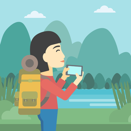 woman cellphone: An asian woman taking photo of landscape with mountains. Young hiking woman with backpack taking photo with her cellphone. Vector flat design illustration. Square layout.