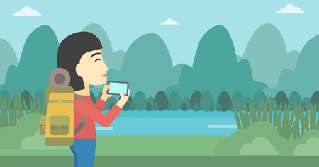 woman cellphone: An asian woman taking photo of landscape with mountains. Young hiking woman with backpack taking photo with her cellphone. Vector flat design illustration. Horizontal layout.