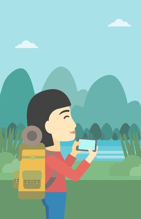 woman cellphone: An asian woman taking photo of landscape with mountains. Young hiking woman with backpack taking photo with her cellphone. Vector flat design illustration. Vertical layout.