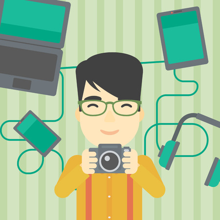 taking photo: An asian young man taking photo with digital camera. Man surrounded with gadgets. Man using many electronic gadgets. Vector flat design illustration. Square layout.