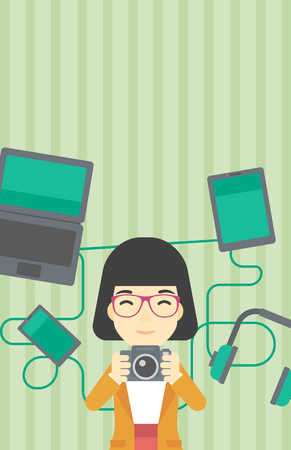 taking photo: An asian young woman taking photo with digital camera. Woman surrounded with her electronic gadgets. Woman using many electronic gadgets. Vector flat design illustration. Vertical layout. Illustration