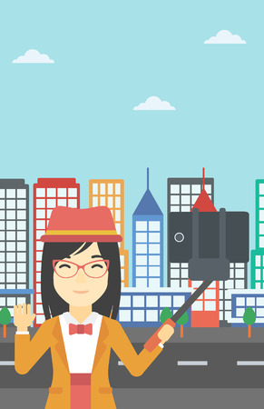 woman cellphone: An asian woman making selfie with a selfie-stick. An asian woman taking photo with cellphone and waving on a city background. Vector flat design illustration. Vertical layout. Illustration