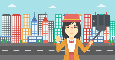 woman cellphone: An asian woman making selfie with a selfie-stick. An asian woman taking photo with cellphone and waving on a city background. Vector flat design illustration. Horizontal layout.