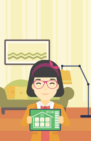 An asian woman showing a tablet computer with smart home application on a screen on the background of living room. Vector flat design illustration. Vertical layout.