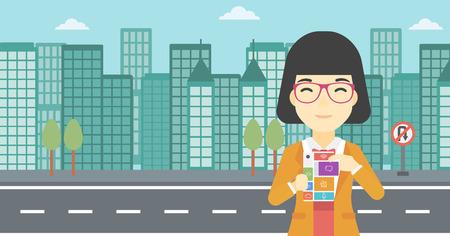 An asian woman holding modular phone. Woman with modular phone standing on a city background. Woman using modular phone. Vector flat design illustration. Horizontal layout.