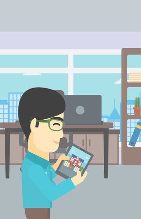 looking at computer: An asian man looking at house on a digital tablet screen. Young man standing in office and looking for house on tablet computer. Vector flat design illustration. Vertical layout. Illustration