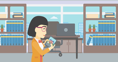 looking at computer screen: An asian woman looking at house on a digital tablet screen. Young woman standing in office and looking for house on tablet computer. Vector flat design illustration. Horizontal layout.