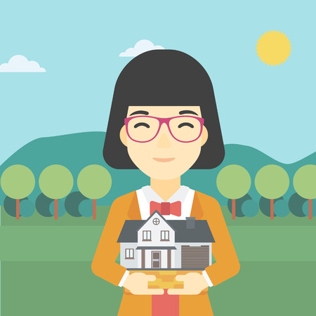 hands holding house: An asian young woman holding house model in hands on the background of mountains. Real estate agent with house model in hands. Vector flat design illustration. Square layout. Illustration