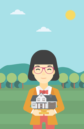 estate agent: An asian young woman holding house model in hands on the background of mountains. Real estate agent with house model in hands. Vector flat design illustration. Vertical layout.