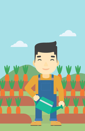 asian farmer: An asian farmer holding a watering can. Farmer watering carrots. Farmer standing on the background of carrots growing on field. Vertical layout.