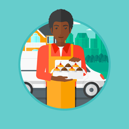 cupcakes isolated: An african-american male baker holding a box of cupcakes on the background of delivery truck. Young baker delivering cakes. Vector flat design illustration in the circle isolated on background.