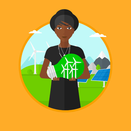 An african-american woman holding light bulb with small wind turbines inside on a background with solar pannels and wind turbines. Vector flat design illustration in the circle isolated on background.