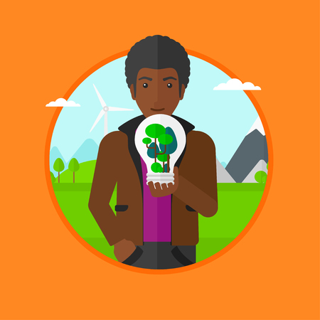 An african-american young man holding light bulb with tree inside on a background with wind turbines. Green energy concept. Vector flat design illustration in the circle isolated on background. Vettoriali